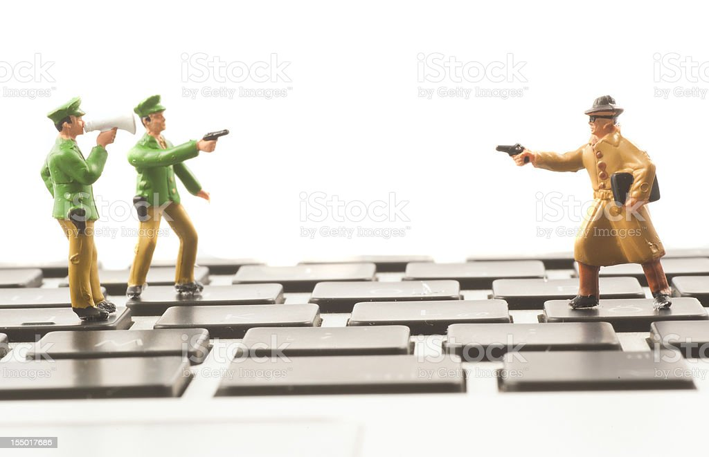 Computer Crime figurines on keyboard abstract stock photo