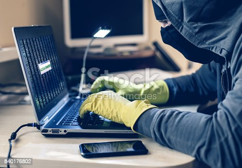 istock Computer Criminal in balaclava and gloves doing protection hack 840176802