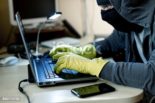 istock Computer Criminal in balaclava and gloves hacking computer 840174730