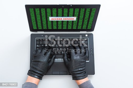 istock Computer Criminal in Gloves working on Laptop Access Denied sign 840176902
