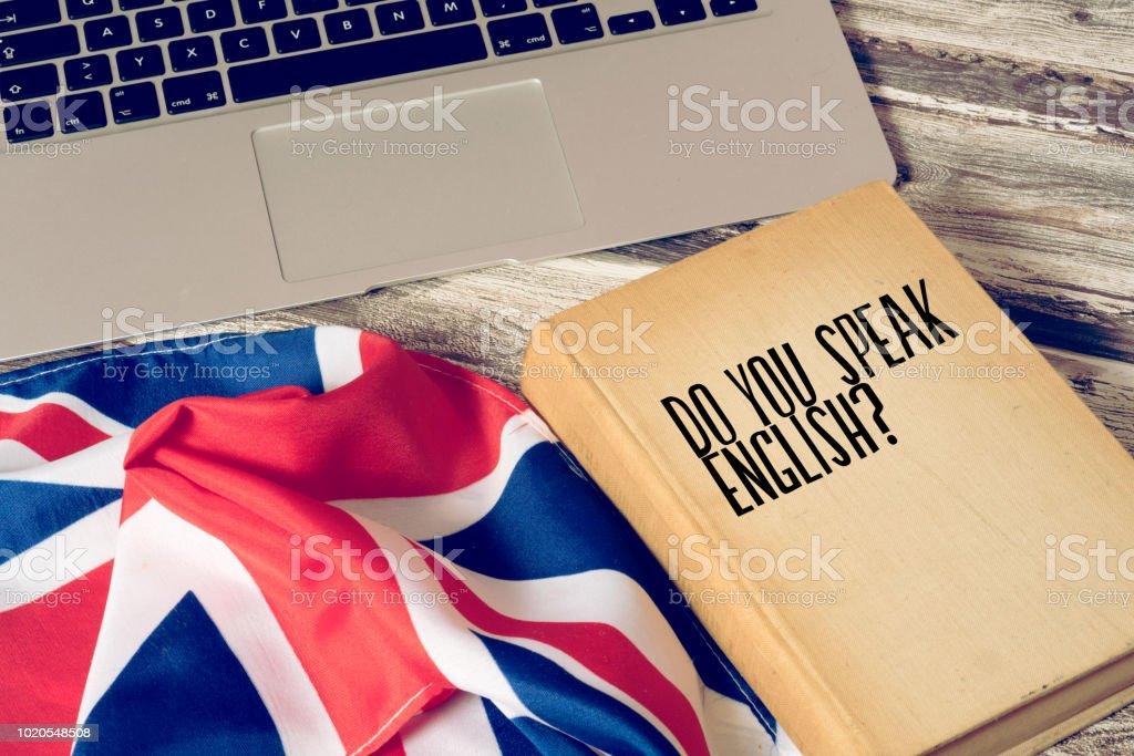 Ein Computer, Flagge von Großbritannien und Buch mit dem Titel Sprechen Sie englisch stock photo