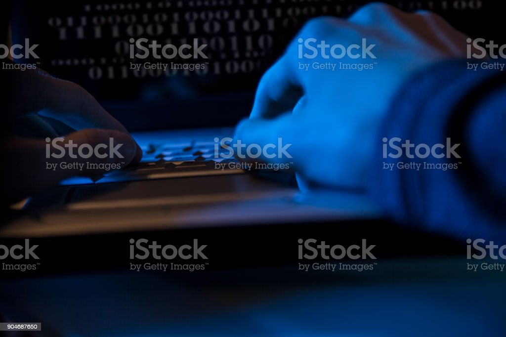 Computer hacker or programmer commits cyber attack using laptop. stock photo