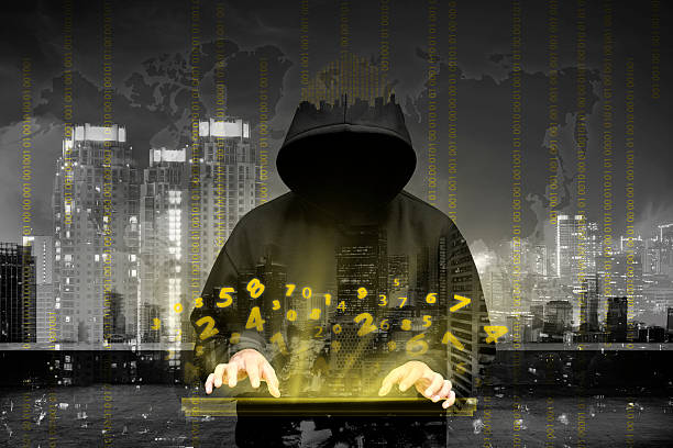 Computer hacker silhouette of hooded man stock photo