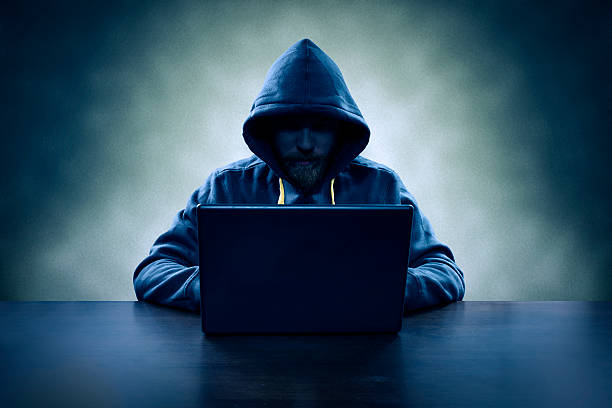 computer hacker stealing information with laptop - hacker stock photos and pictures