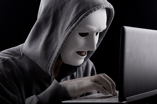 Computer Hacker With Mask Pressing Komputer Buttons Stock Photo - Download Image Now