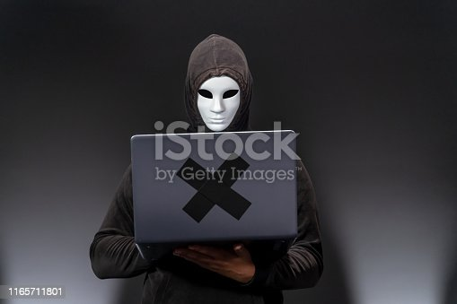 istock Computer hacker with mask stealing information with laptop 1165711801