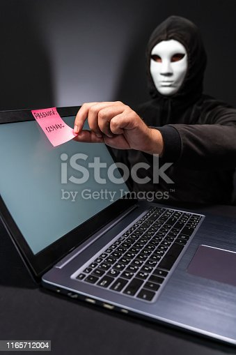 istock Computer hacker with mask taking a pink note with weak password 1165712004