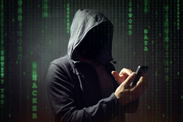 computer hacker with mobile phone - hacker stock photos and pictures