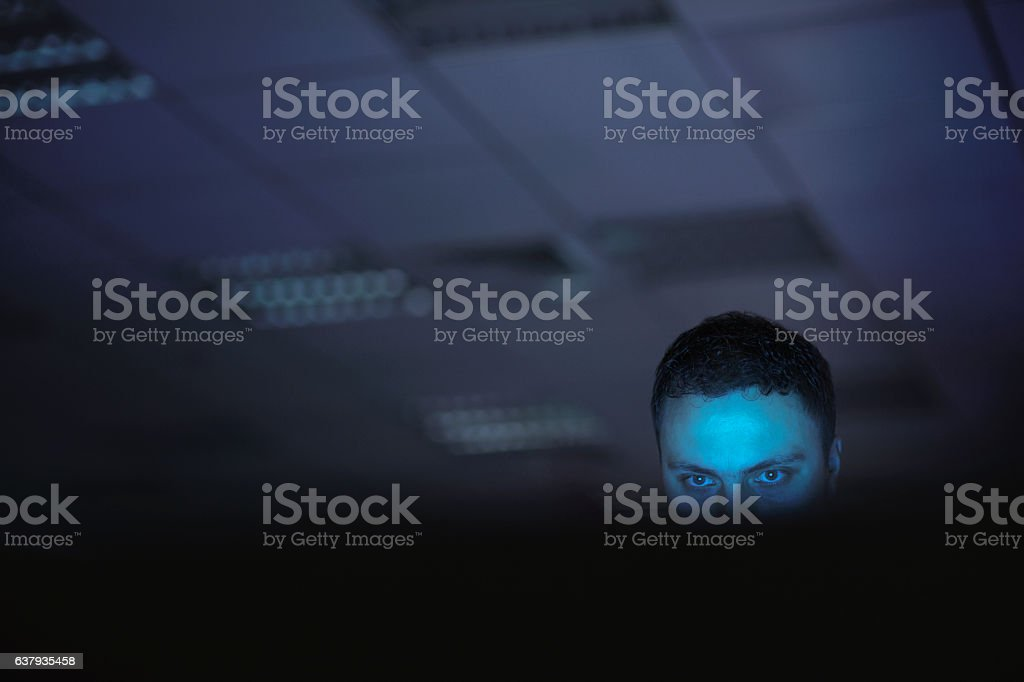 Computer hacker working on laptop late at night in office - foto de stock