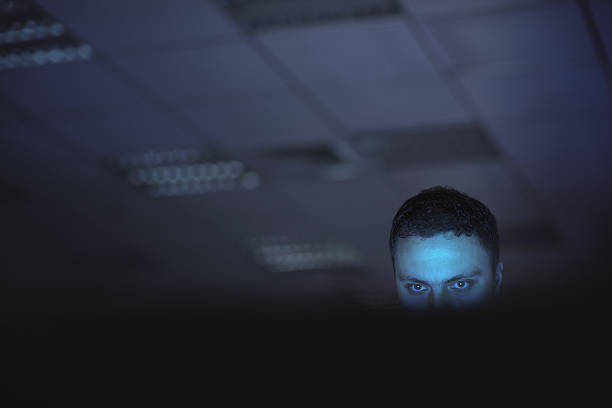 computer hacker working on laptop late at night in office - enigma images stock photos and pictures