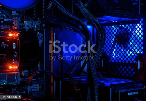 Computer illuminated by internal LED RGB lights, hardware inside open high performance desktop PC. The open tower of gaming computer for wallpaper. Concept of computer repair and modern technology.