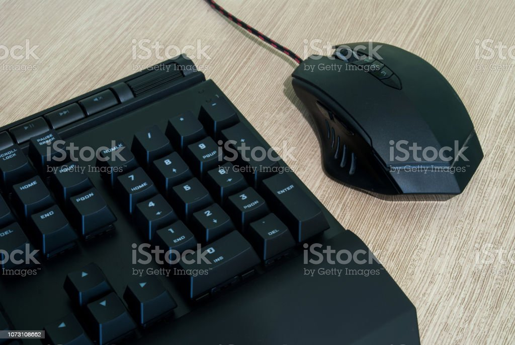 Computer keyboard and mouse on wooden background
