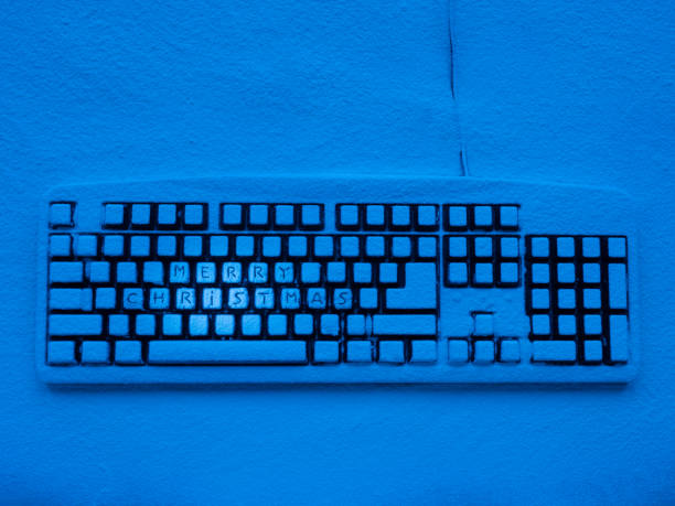 computer-tastatur bedeckt mit schnee mit blauem neonlicht mit text beleuchtet frohe weihnachten - weihnachtsprogramm stock-fotos und bilder