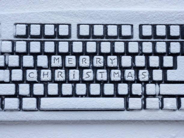 computer-tastatur mit weißen schnee mit inschrift bedeckt frohe weihnachten - weihnachtsprogramm stock-fotos und bilder