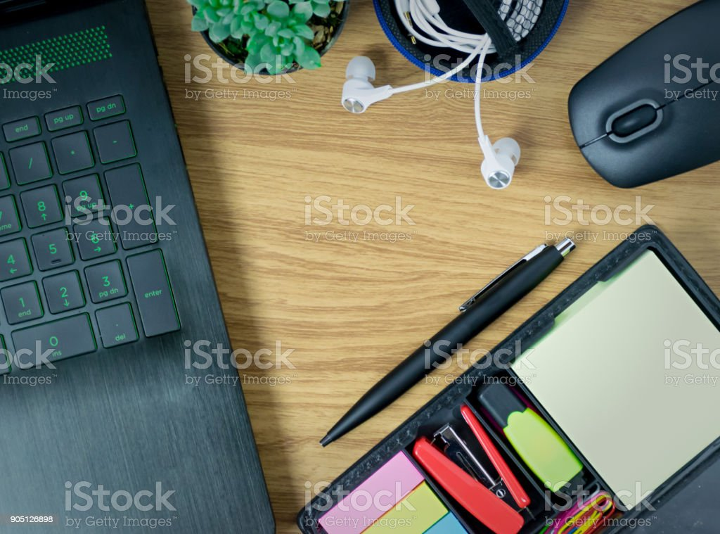 computer Laptop a mouse of cactus the pen and earphone on the wood table stock photo