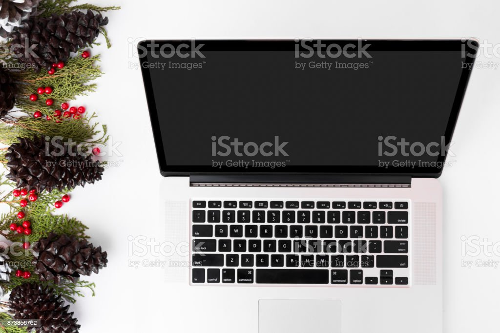 Computer laptop mobile display on table with isolated white screen for mockup in Christmas time. Christmas tree, gifts, decorations in background. stock photo