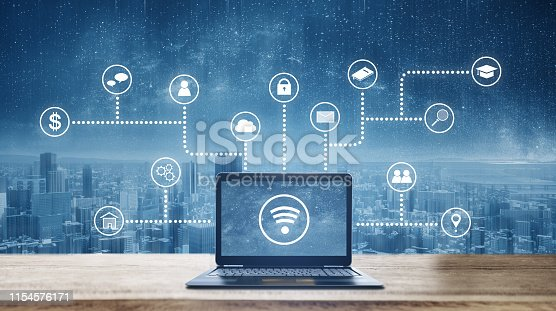 Computer laptop on wooden desk with wireless and application programming and social media icons. Internet networking and wireless technology