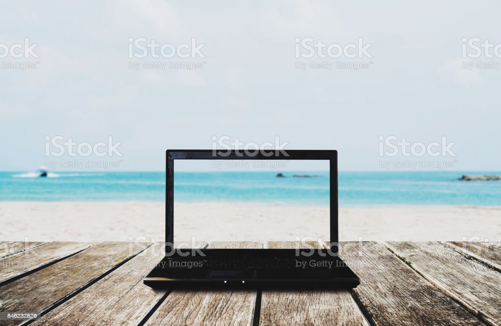 Computer laptop on wooden table with the beach view background. Clipping path on screen stock photo