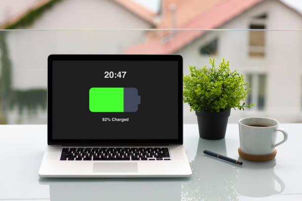 computer laptop mit geladener batterie bildschirm auf tisch im café - sinnvolle wörter stock-fotos und bilder