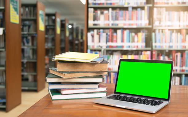 Computadora portátil con pantalla verde y pila de libros en la biblioteca room.education concepto de fondo - foto de stock