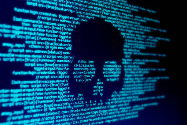Computer Malware Attack Computer code on a screen with a skull representing a computer virus / malware attack. computer crime stock pictures, royalty-free photos & images