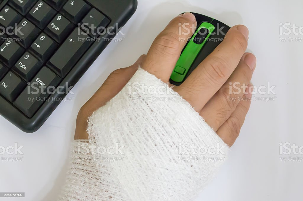 computer mouse in male bandaged hand stock photo