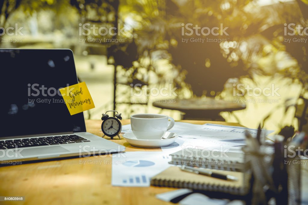 computer notebook, clock, cup of coffee and graphs papers put on wooden table. there is post it paper and wording 'Good Morning' on laptop screen. stock photo