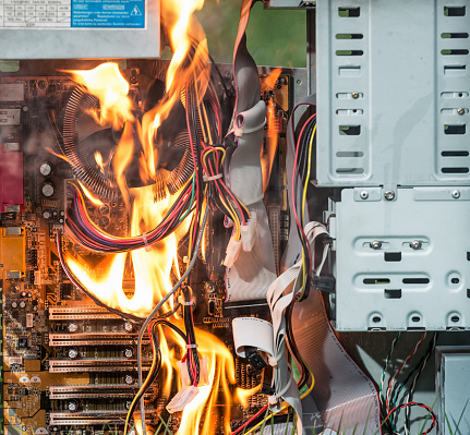 The motherboard and other internal components of a PC being destroyed by fire.