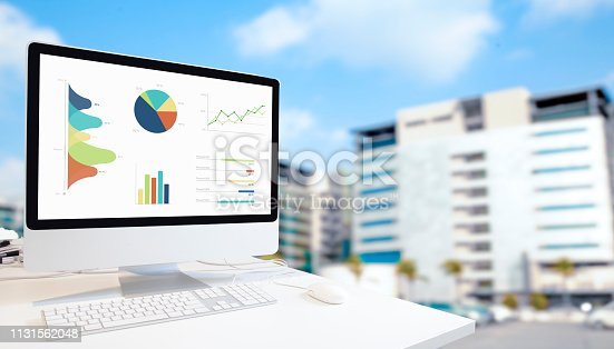 1133586715istockphoto Computer on  table showing charts and graph 1131562048