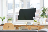 Image of big computer monitor on the wooden table at office