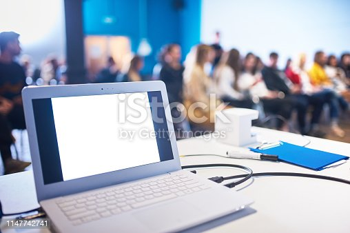 478810450 istock photo Computer on the table, blur image of conference room with people as background. 1147742741