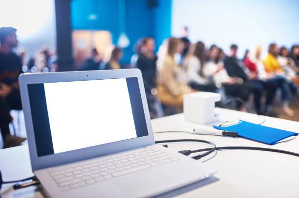 Ordinateur sur la table, image floue de la salle de conférence avec les gens comme arrière-plan. - Photo