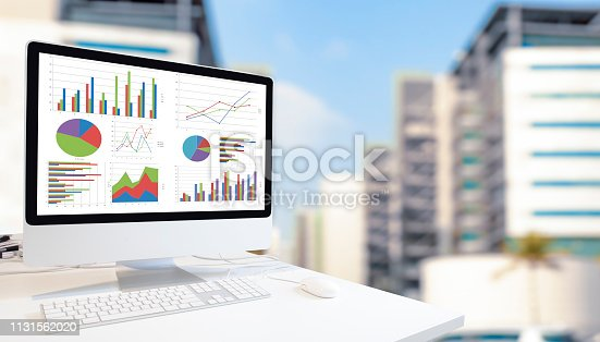 1133586715istockphoto Computer on wooden table showing charts and graph 1131562020