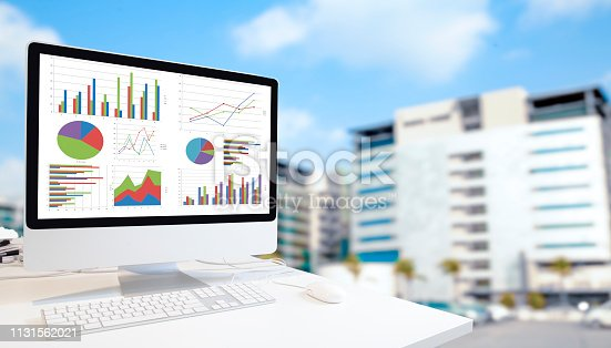 1133586715istockphoto Computer on wooden table showing charts and graph 1131562021