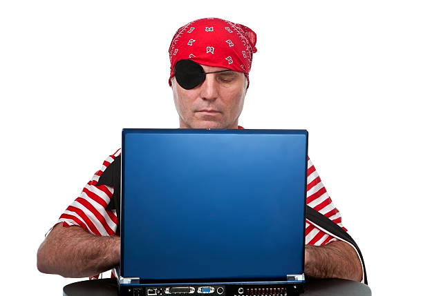 computer pirate a pirate looking down at a laptop computer costume eye patch stock pictures, royalty-free photos & images