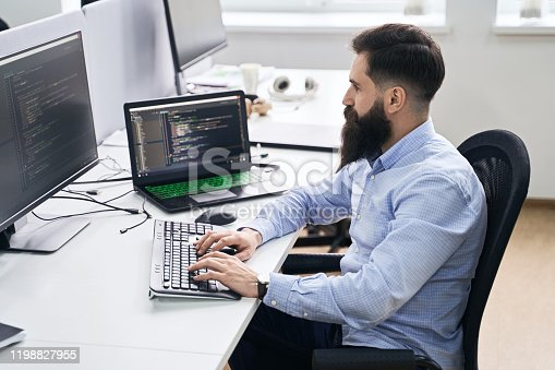 istock Computer programmer developer working in IT office, sitting at desk and coding, working on a project in software development company or startup. 1198827955
