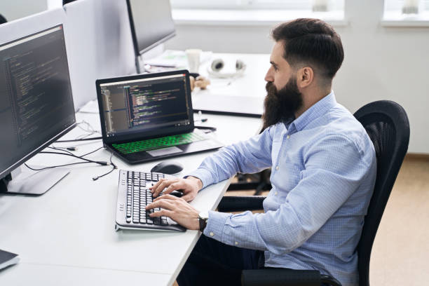 Computer programmer developer working in IT office, sitting at desk and coding, working on a project in software development company or startup. stock photo