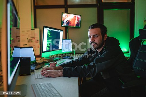 Young professional hacker working in his hidden office