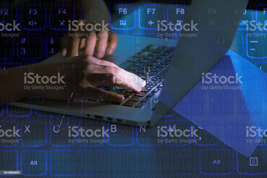 A computer programmer or hacker prints a code on a laptop keyboard to...