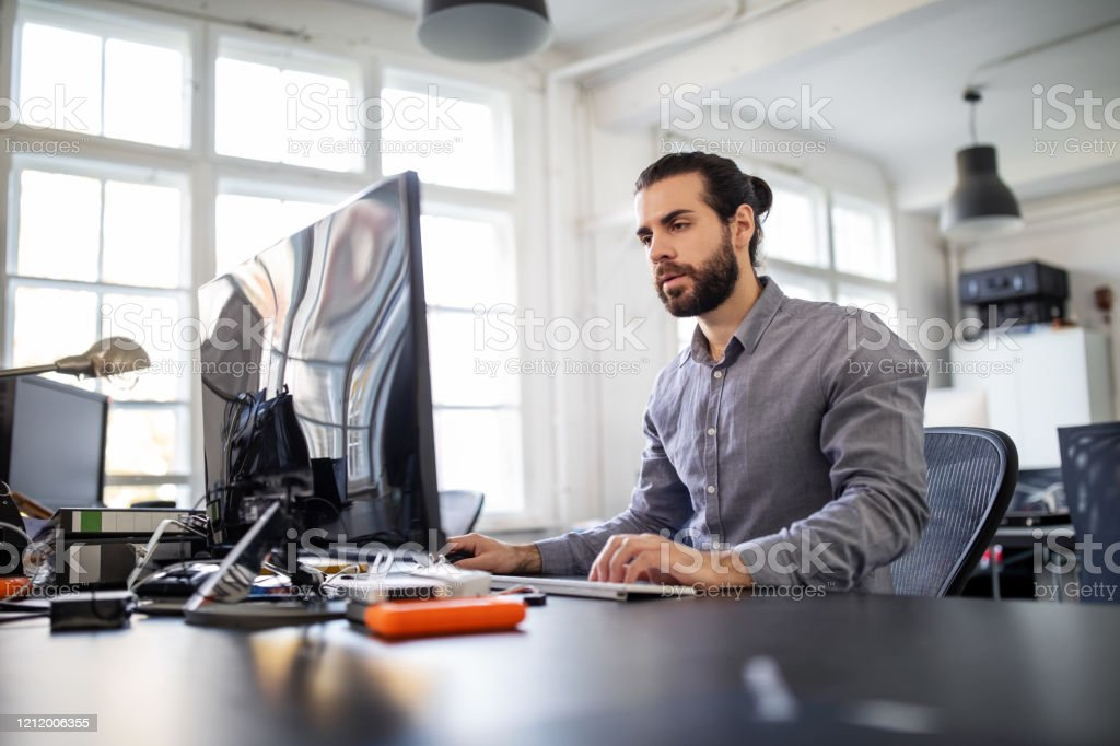 Computer programmer working at his desk - Royalty-free 25-29 Years Stock Photo
