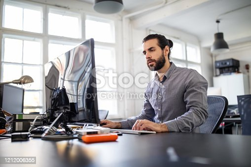 Young businessman sitting at his work desk and working on desktop computer. Male executive looking at camera and smiling while working on computer..