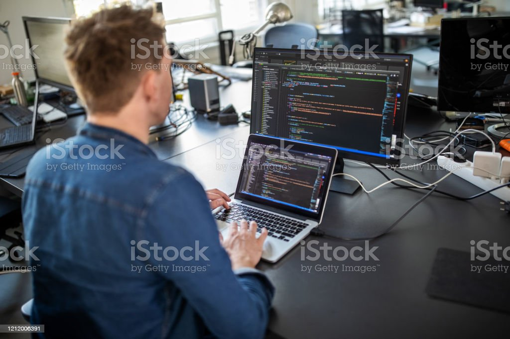 Computer programmer working on new software program Businessman working on laptop and looking at desktop computer monitor. Male professional sitting at his office desk and working on new software program. Technology Stock Photo