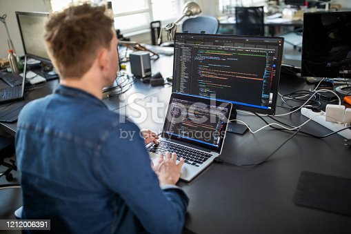 Businessman working on laptop and looking at desktop computer monitor. Male professional sitting at his office desk and working on new software program.