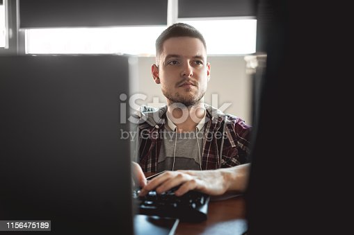 872006502 istock photo computer programmer. young man working in office. 1156475189