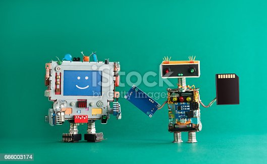 istock Computer repair renovation concept. Smiling monitor machine, robot serviceman with chip circuit storage memory card device. green background 666003174