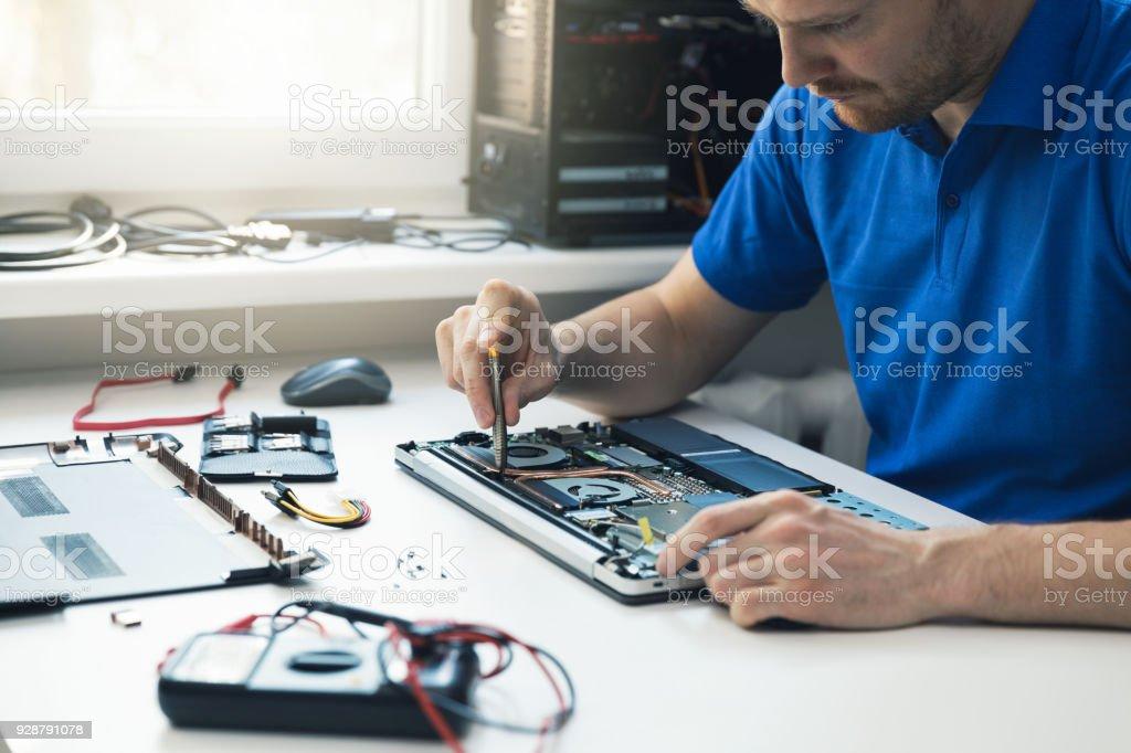 computer repair service - technician repairing broken laptop in office stock photo