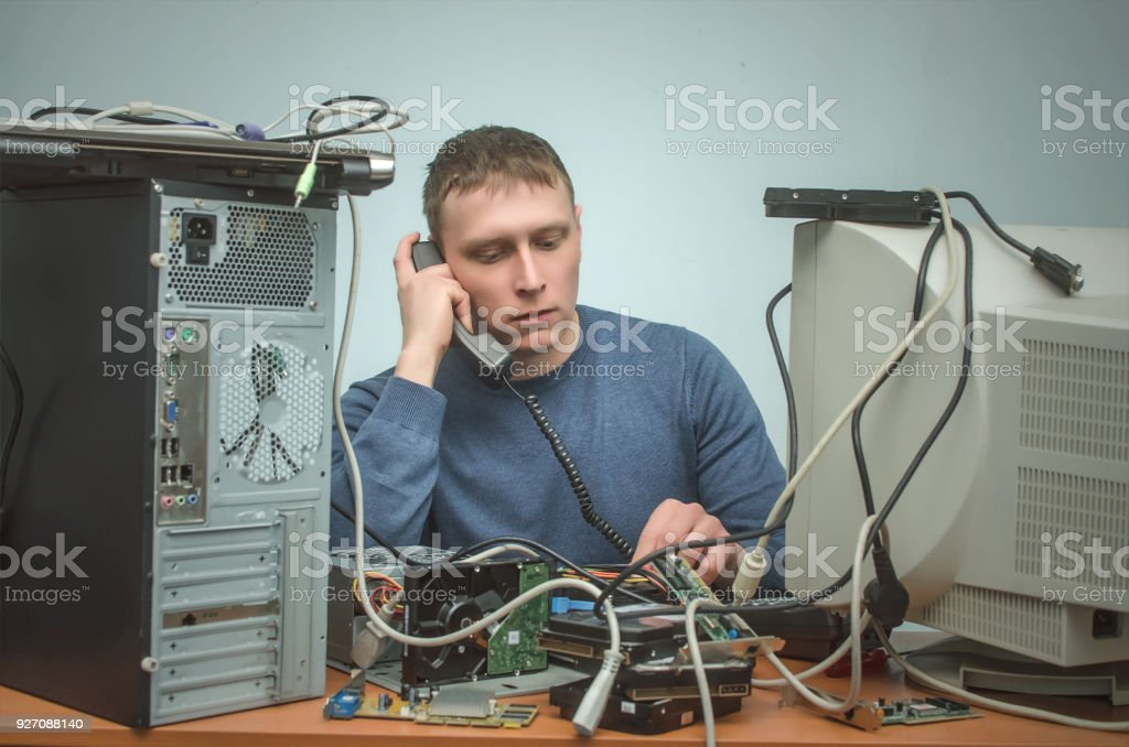 Tired and bored computer technician engineer is sitting on his...
