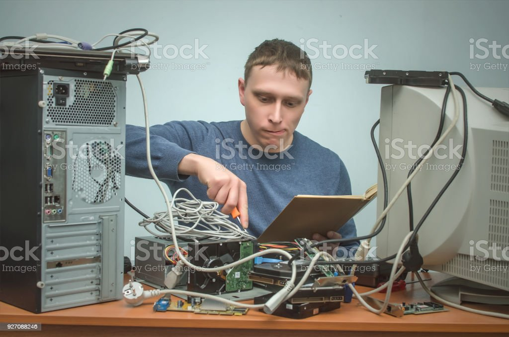 Computer technician holding in hands a manual book and is installing...