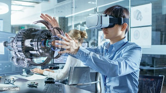 istock Computer Science Engineer wearing Virtual Reality Headset Works with 3D Model Hologram Visualization, Makes Gestures. In the Background Engineering Bureau with Busy Coworkers. 968289756