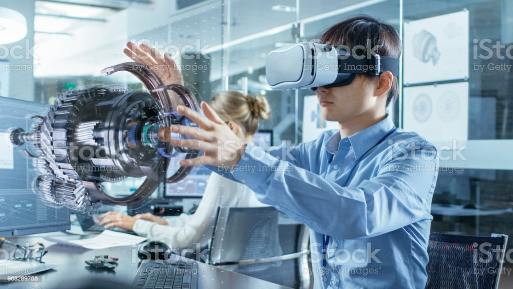 Computer Science Engineer wearing Virtual Reality Headset Works with 3D Model Hologram Visualization, Makes Gestures. In the Background Engineering Bureau with Busy Coworkers. stock photo